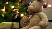 ribbon : Teddy bear on the background of Christmas tree with a garland Stock Footage