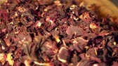carmesim : Hibiscus tea is a herbal tea made as an infusion from crimson or deep magenta-colored calyces (sepals) of the roselle (Hibiscus sabdariffa) flower. It is consumed by both hot and cold.