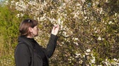 blooming : Young woman near a flowering tree. Stock Footage