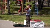 com cordas : Mariupol, Ukraine - April 30, 2018: Boy on the street playing the violin.
