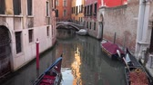 венето : Venice, Italy - March 23, 2018: Tourists in the gondolas swim through the narrow canals in Venice