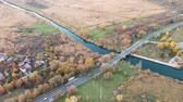 ストリート : Aerial video. Traffic on the bridge over a small river. Autumn.