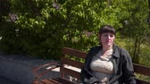 humano : A young woman sits on a bench. In the background is a blooming lilac Archivo de Video
