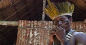 guarani : Native Brazilian playing wooden flute at an indigenous tribe in the Amazon Stock Footage