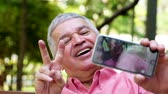 brasileiro : Hispanic senior taking selfie photos in the park