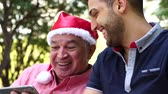 Father with santa hat and his son having fun in a park