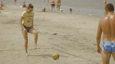 тонкий : Girl is playing football with her boyfriend on the beach
