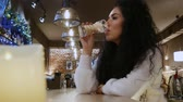 one person only : Beautiful curly-haired girl is waiting in the restaurant. Cute brunette in a white sweater in a winter cafe Stock Footage