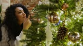 tutmak : Attractive curly-hair girl looks at New Year tree. Beautiful brunette in a white sweater enjoys a beautiful toys Stok Video
