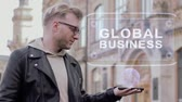 visualização : Smart young man with glasses shows a conceptual hologram Global Business. Student in casual clothes with future technology mobile screen on university background Stock Footage