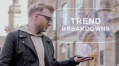 složitost : Smart young man with glasses shows a conceptual hologram Trend breakdowns. Student in casual clothes with future technology mobile screen on university background