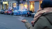 stoupenec : Unrecognizable woman standing on the street interacts HUD hologram with text Subscribe. Girl in warm clothes with a scarf uses technology of the future mobile screen on background of night city