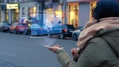 implemento : Unrecognizable woman standing on the street interacts HUD hologram with dumbbells. Girl in warm clothes with a scarf uses technology of the future mobile screen on background of night city Stock Footage