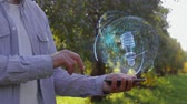 lâmpada elétrica : Unrecognizable man shows conceptual hologram with gas discharge bulb. Farmer on the background of the apple orchard in casual clothes with the technology of the future mobile screen Stock Footage