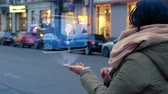 zang : Unrecognizable woman standing on the street interacts HUD hologram with microphone. Girl in warm clothes with a scarf uses technology of the future mobile screen on background of night city