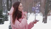 revisão : Beautiful young woman in a winter park interacts with HUD hologram with text Data integration. Red-haired girl in warm pink clothes uses the technology of the future mobile screen