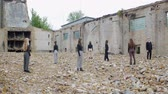 sect : Group of young people stand in the ruins of an apocalypse post on the ground, Young people in black are turned around against the background of a collapsed building and scattered bricks Stock Footage