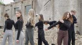 sect : Group of young people in the ruins of an apocalypse post on the ground, Young people in black against the background of a collapsed building and scattered bricks
