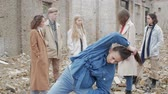 sect : Young woman in blue performs a dance among a group of young people in the ruins. The youth makes a theatrical sketch against the background of a collapsed building of bricks