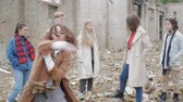 sect : Curly woman in a coat performs a dance among a group of young people in the ruins. The youth makes a theatrical sketch against the background of a collapsed building of bricks