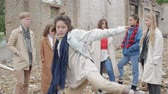 sect : Young woman in blue scarf performs a dance among a group of young people in the ruins. The youth makes a theatrical sketch against the background of a collapsed building of bricks Stock Footage