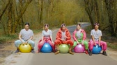kugel : A happy company of friends in bright ski suits sings fun on bright balls on a forest road in sunny weather. Young people musicians in goggles with colorful balls in the forest