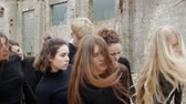 sect : Group of young people in black waving their heads in the ruins slow motion. Young people in black waving their hair standing against the background of a collapsed building of bricks Stock Footage