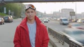 momento : Portrait of a young man in a red jacket on the background of the road and the city timelapse. Attractive guy in ski goggles calmly looking into the camera Stock Footage