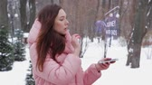 uygulanması : Beautiful young woman in a winter park interacts with HUD hologram with text Journey never ends. Red-haired girl in warm pink clothes uses the technology of the future mobile screen Stok Video