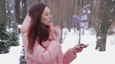 sabedoria : Beautiful young woman in a winter park interacts with HUD hologram with text Learn Chinese. Red-haired girl in warm pink clothes uses the technology of the future mobile screen Vídeos