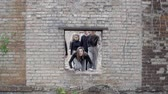 sect : Group of young people are approaching a hole in the wall of the post of the apocalypse on the ground. Young people in black are climbing into the window of a brick wall. Freedom concepts Stock Footage