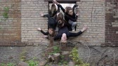 sect : Freedom concepts. Group of young people in a hole in the wall of the post of the apocalypse on the ground. Young people in black into the window of a brick wall