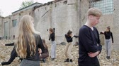 sect : Young people in black against a collapsed building and scattered bricks. A group of young people in the ruins of the fast of the apocalypse on earth. The concept of broken relationships Stock Footage
