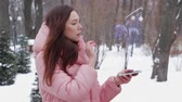optometria : Beautiful young woman in a winter park interacts with HUD hologram eyeglasses. Red-haired girl in warm pink clothes uses the technology of the future mobile screen
