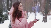 報奨金 : Beautiful young woman in a winter park interacts with HUD hologram safe with money. Red-haired girl in warm pink clothes uses the technology of the future mobile screen