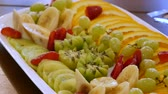 киви : Sliced bananas, oranges, grapes, kiwi, strawberries close-up. delicious food on the table. A dish of fresh fruit at the festive dining table. Assorted sliced fruits on a plate