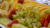 киви : Assorted sliced fruits on a plate. Sliced bananas, oranges, grapes, kiwi, strawberries close-up. delicious food on the table. A dish of fresh fruit at the festive dining table
