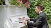 compositor : Play the piano in nature. Cute young man playing an old white piano. A focused pianist plays melodies. Pleasant sunshine through the trees. Professional virtuoso for piano