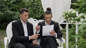 pavilion : Businessmen sign a contract on a luxurious armchair in a white arbor. Entrepreneur and businessman talk, draw up a contract, sign documents, complete a deal