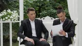 partnership : Young businessmen sign a contract on a luxurious armchair in a white arbor. Entrepreneur and businessman talk, draw up a contract, sign documents, draw up a deal, shake hands
