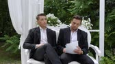 роскошный : Two businessmen sign a contract on a luxurious armchair in a white arbor. Entrepreneur and businessman talk, draw up a contract, sign documents, draw up a deal, shake hands