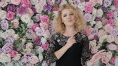performs : Elegant curly blonde sings near a wall of flowers. Young woman singer sings on the background of flowers. Girl in a black evening dress with flowers