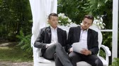 роскошный : Two businessmen sign document on a luxurious armchair in a white arbor. Entrepreneur and businessman draw up a contract, sign documents, draw up a deal