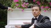 соло : A man sits on a chair next to the piano and sings. Singer in costume sings on white piano background Стоковые видеозаписи