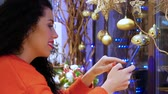 送信 : Young smiling curly woman in a red sweater and with red lips with a phone on the background of Christmas decor. Girl holding a smartphone on New Years Eve