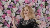 flower growing : Cute young woman singer sings emotionally on the background of flowers. Elegant curly blonde sings near a wall of flowers. Girl in a black evening dress with flowers Stock Footage