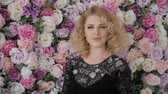 performs : Cute young woman looking at the frame emotionally on a background of flowers. Elegant curly blonde near the wall of flowers. Girl in a black evening dress with flowers