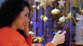送信 : Young smiling curly woman looking at phone on the background of Christmas decor. Videocall, streaming live. Girl in a red sweater and with red lips holding a smartphone on New Years Eve