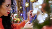 送信 : Young serious curly woman in glasses, a red sweater and with red lips with a phone on a background of Christmas decor. Girl holds smartphone on New Years Eve