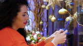 送信 : Girl holding a smartphone on New Years Eve. Young smiling curly woman in a red sweater and with red lips with a phone on the background of Christmas decor